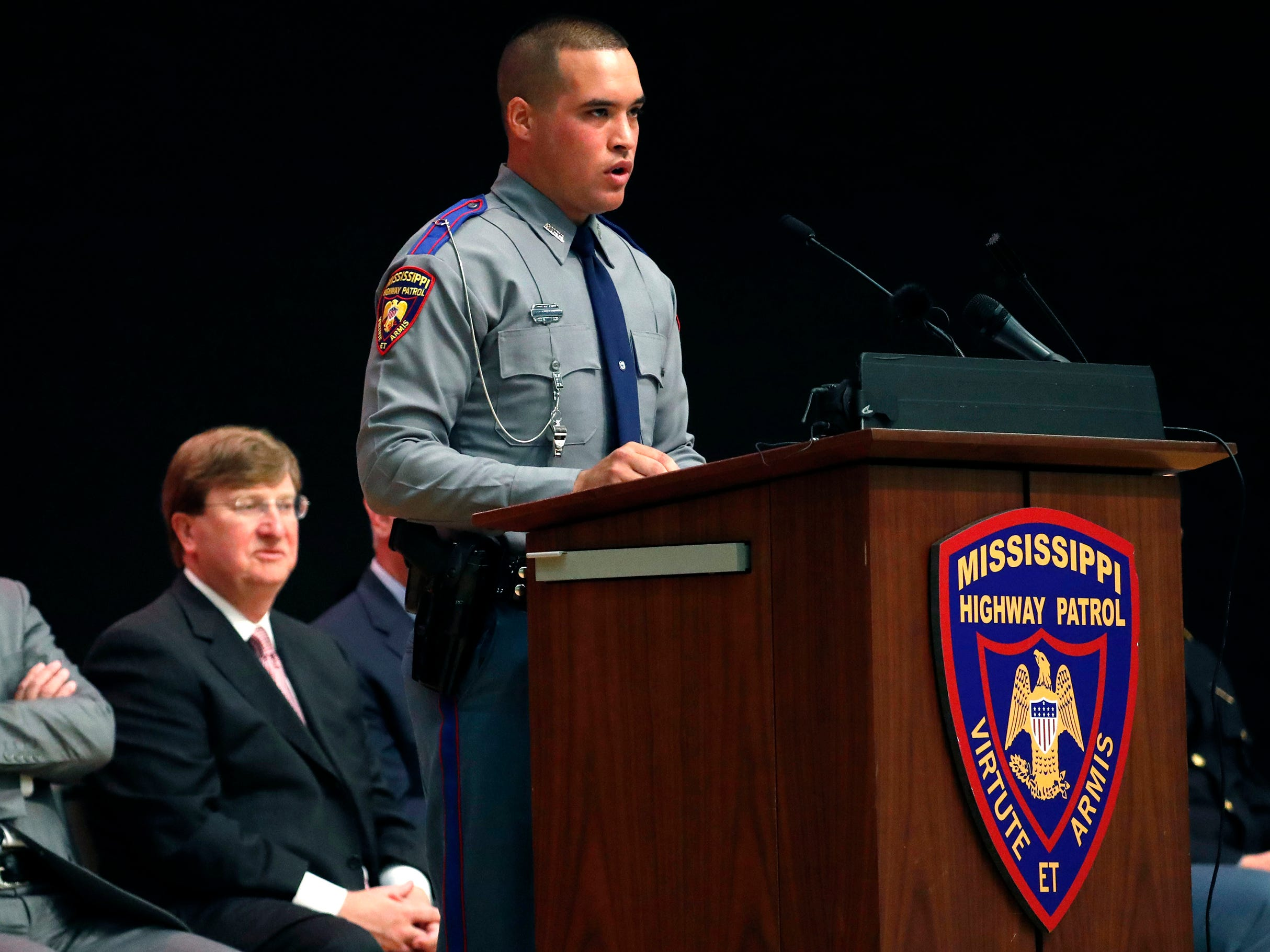 Gov. Phil Bryant, left, and Lt. Gov. Tate Reeves, second from left, listen as Cadet Landon Orozco, Class 63 president, delivers a class response following the governor's address, during the Mississippi Highway Patrol cadets' graduation ceremony, Wednesday, May 1, 2019, at the Clyde Muse Center in Pearl, Miss. The patrol's training lasts 22 weeks and involves classroom instruction, physical fitness, firearms and emergency operations training as well as a variety of police science courses. The state's newest 44 troopers include 4 women.