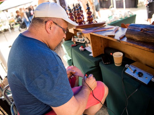 Joe Compton engraves one of the wooden spoons he makes and sells at the Market Square Farmers Market, which had its opening day in downtown Knoxville, on Wednesday, May 1, 2019.