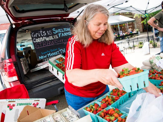 Sharon Shelton of Shelton Farms bags a carton of strawberries for a customer at the Market Square Farmers Market in downtown Knoxville on Wednesday, May 1, 2019.