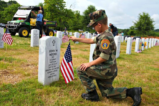 Lance Corporal Henry Webster takes time to think about the project of placing flags on the graves of veterans for Memorial Day.