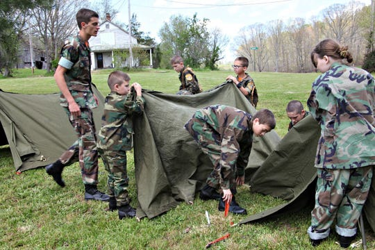 After an overnight adventure, Young Marines use teamwork to get the tents folded.