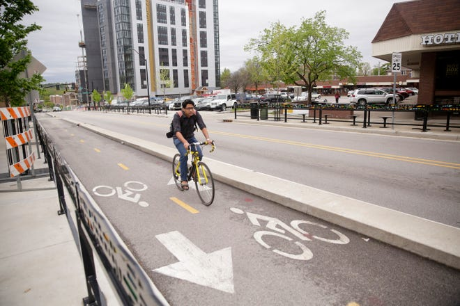 A bicyclist pedals up W. State st. in the dedicated two-way bike lane, Wednesday, May 1, 2019 in West Lafayette. West Lafayette is considering a series of ways to protect cyclists, including fines for careless driving, ahead of Bicycle Friendly Community application.
