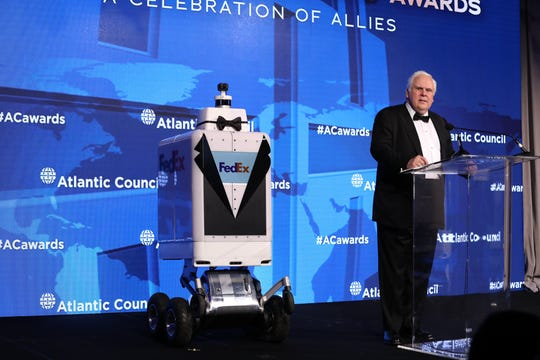 A FedEx SameDay Bot in formal attire carried FedEx founder and CEO Fred Smith's Distinguished Business Leadership Award from international affairs think tank Atlantic Council to the stage on Tuesday.