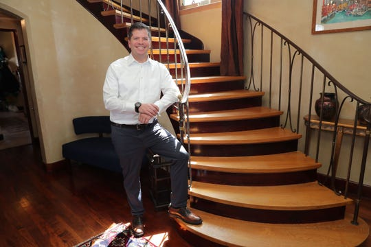 Matt D'Attilio stands in front of the curved stairway that helped sell him on purchasing the house back in 2004.
