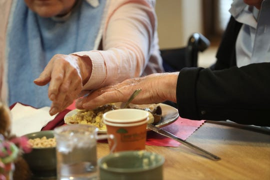 Former Gov. Marty Schreiber uses his hand to keep his wife's sleeve out of her food as she reaches for a cereal bowl. Elaine Schreiber has Alzheimer's disease.