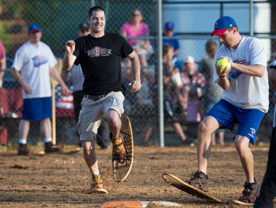 Snowhawks pitcher Craig Holmquist (right) races to first base for a forced out by The Brick's T.J. Lelonek during their snowshoe baseball game June 22, 2015, in Lake Tomahawk.