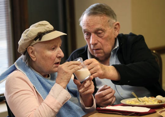 Former Wisconsin Gov. Marty Schreiber helps his wife, Elaine, with a glass of milk during breakfast April 1 at Lutheran Home in Wauwatosa. She is suffering from Alzheimer's disease.