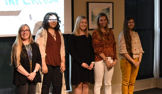 Art instructor Beth Ivens, (far left) and Mountain Home High School art students (from left) Breanna Hickmott, Ava Obert, Grace Hilvert and Lakeisha Ponce get a round of applause from the Friends of the North Fork and White Rivers on Monday night.