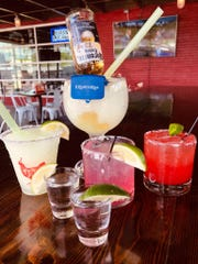 Party Fowl's Coronita is a margarita made with Riunite and a bottle of Corona turned upside down. Also pictured are the frozen, prickly pear and strawberry margaritas with shots of tequila.