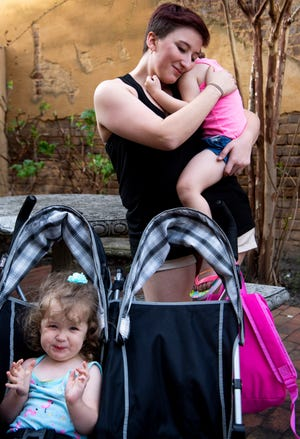 Courtney Conner holds her daughter Trinity, 3, while her other daughter, Lynli, 2, sits in the stroller during their afternoon walk around downtown Greeneville, Tenn., on April 11, 2019. Conner describes her daughters as daredevils and said she needs to live close to a hospital in case they're injured.
