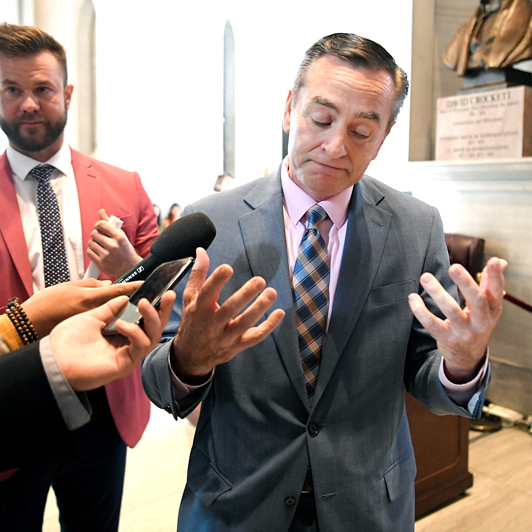Reporters follow and ask questions of House Speaker Glen Casada, right, regarding a bill during the legislative session May 1, 2019. Casada's then chief of staff, Cade Cothren, stands at left.