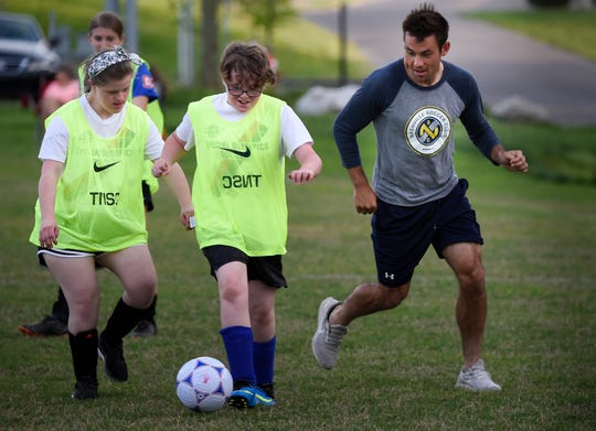 Special olympians Randle Webber 22, and Daniel Varnell 10, speed past Nashville SC defender Taylor Washington during a soccer clinic at Flagpole Park Tuesday, April 30, 2019 in Brentwood, Tenn.