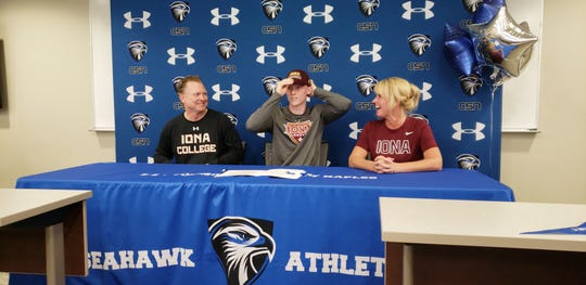 Community School of Naples basketball player puts on an Iona hat after signing with the Division I college program on Wednesday. He is seated with his parents Bart and Kathy Weiss.