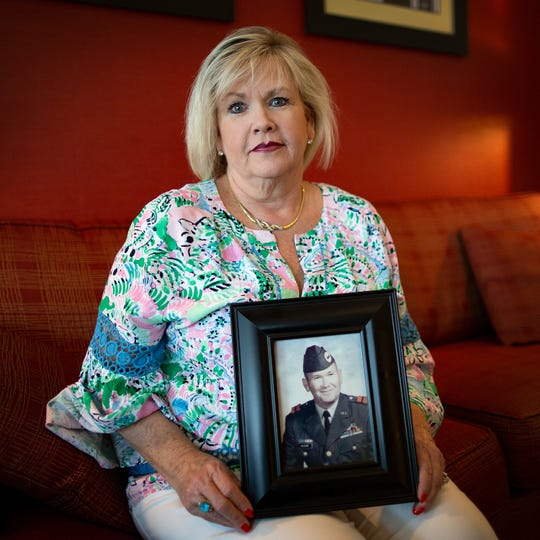 Linda Couchot holds a picture of her late father, retired Master Sgt. Robert E. McCort, in Jacksonville, Fla., on Friday April 26, 2019.  Couchot had to fight with a financial institution over her father's home.