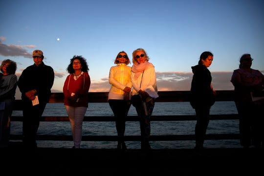 Lana Butsky, center left, and Connie Leon, center right, enjoy the sunrise during an Easter Sunday service hosted by the First United Methodist Church at the Naples Pier on April 21, 2019.