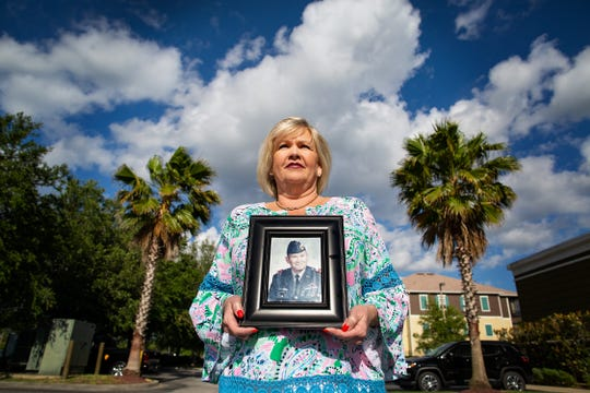 Linda Couchot holds a picture of her late father, Retired Master Sgt. Robert E. McCort in Jacksonville, Fla., on Friday, April 26, 2019. Couchot had to fight with a financial institution over her father's home.