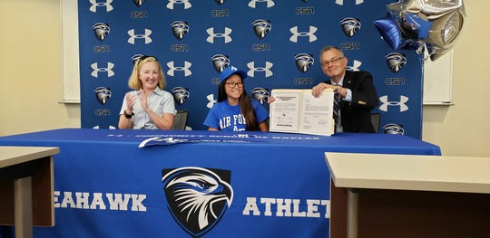 Mike Carr shows off the letter of intent his daughter Katherine (middle) signed to join the Air Force Academy diving team on Wednesday. Katherine's mother, Stephany Carr, is on the left.