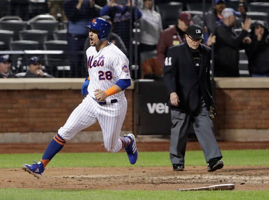New York Mets' J.D. Davis celebrates after scoring the winning run on a sacrifice fly by Pete Alonso during the 10th inning of the team's baseball game against the Cincinnati Reds on Tuesday, April 30, 2019, in New York. The Mets won 4-3. (AP Photo/Frank Franklin II)