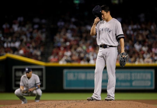 New York Yankees' Gio Urshela kneels as starting pitcher Masahiro Tanaka adjusts his cap after giving up a run on a wild pitch against the Arizona Diamondbacks during the second inning of a baseball game, Wednesday, May 1, 2019, in Phoenix.