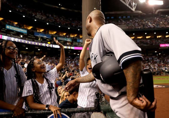 New York Yankees starting pitcher C.C. Sabathia greets his kids after throwing his 3,000th career strikeout, during the second inning of the team's baseball game against the Arizona Diamondbacks, Tuesday, April 30, 2019, in Phoenix.