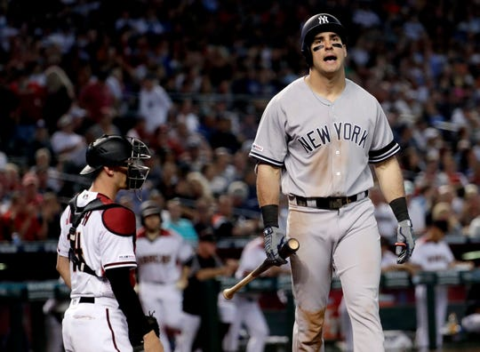 New York Yankees Gio Urshela walks to the dugout after striking out as Arizona Diamondbacks catcher Caleb Joseph looks to the mound during the sixth inning of a baseball game, Wednesday, May 1, 2019, in Phoenix.