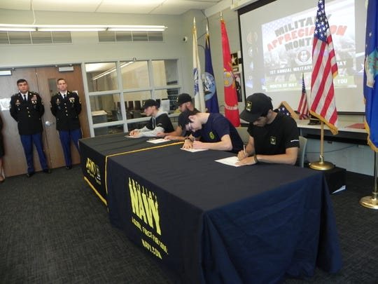 Four seniors from Henry P. Becton Regional High School sign their enlistment papers at the school's first annual Military Signing Day. From left, Cole Willis, Sebastian Cardona, Matt Chattaway and Kier Alexander. 5/1/19