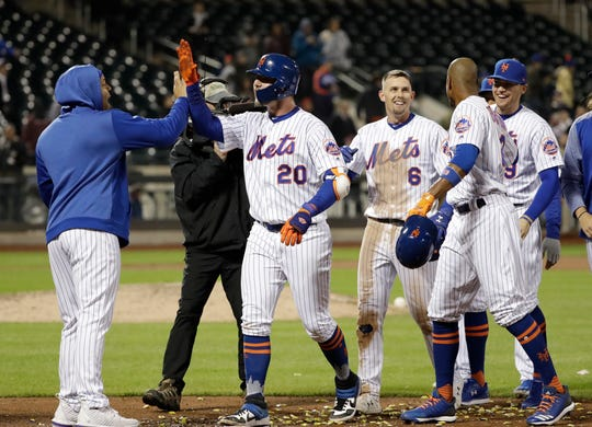 New York Mets' Pete Alonso (20) and Jeff McNeil (6) celebrate with teammates after the Mets won 4-3 on a sacrifice fly ball by Pete Alonso during the 10th inning of a baseball game against the Cincinnati Reds on Tuesday, April 30, 2019, in New York. (AP Photo/Frank Franklin II)