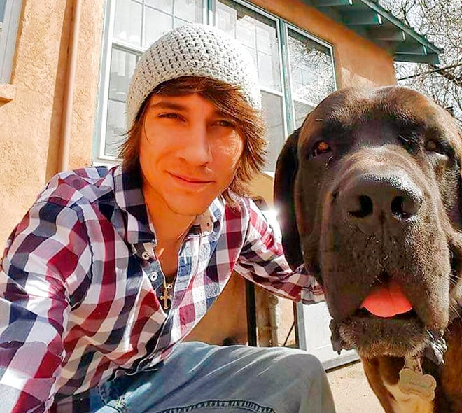 This 2018 photo provided by Bobby Berridge shows his son, Joseph Berridge, with his dog Lucious in Albuquerque. N.M. Bobby Berridge says his son was the pilot who died when a Hawaii tour helicopter crashed on a residential street in Kailua, a suburb of Honolulu on Monday, April 29, 2019. He says his son moved to Hawaii two weeks ago to fulfill a dream of being a tour helicopter pilot. The Honolulu medical examiner's office hasn't released the names of the three aboard who died.