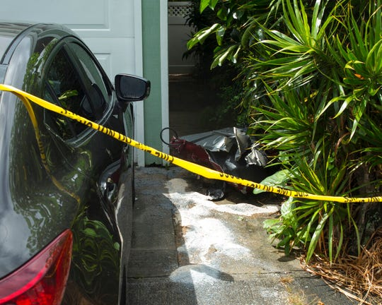 Debris lies on the ground where parts of a helicopter hit a parked car, Monday, April 29, 2019, in Kailua, Hawaii. Fire and helicopter parts rained from the sky Monday in a suburban Honolulu community in a crash that killed three people aboard, officials and witnesses said.