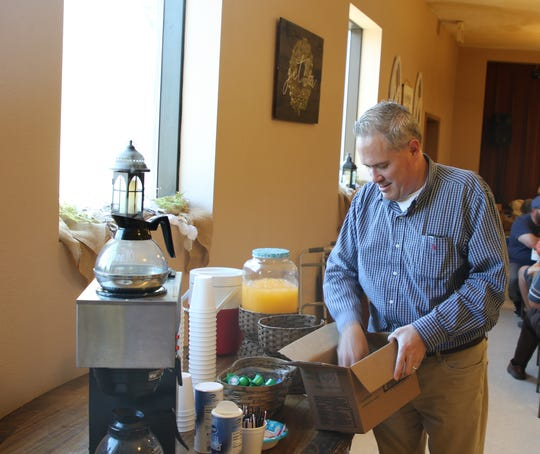 Pastor Daniel Phelps provides coffee creamer during the 108th May Day Breakfast at First Evangelical Presbyterian Church May 1.