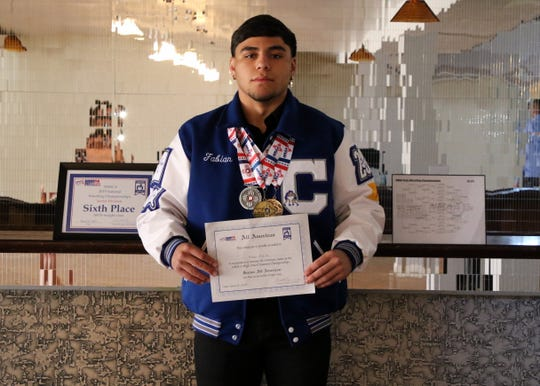 Fabian Padilla showcases his senior wrestling awards. On the left is his sixth-place finish at Virginia Beach. On his right is his State Championship bracket. He holds his All-American wrestler certificate and wears his three state wrestling medals around his neck.