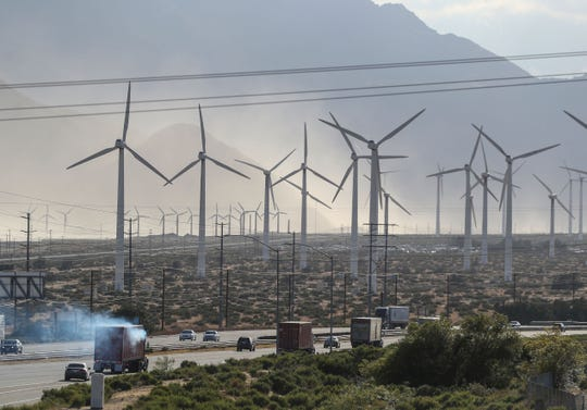 Traffic travels along Interstate 10 as high winds push sand into the air around the windmills outside of Palm Springs, April 30, 2019.