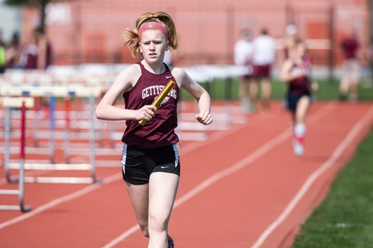 Gettysburg's Autumn Oaster competes in the 3200m relay during a YAIAA track and field meet against New Oxford Tuesday, April 30, 2019.