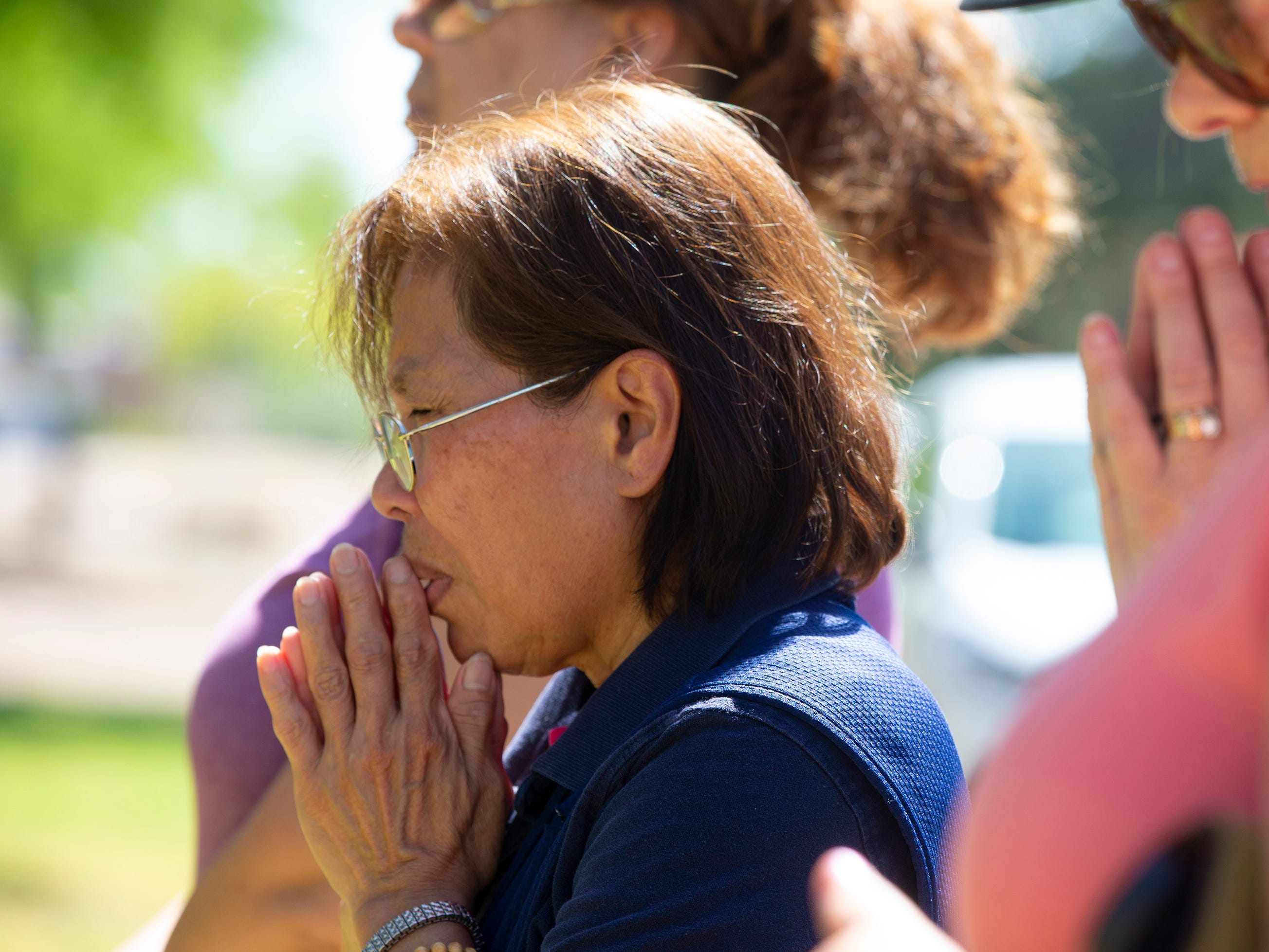 Parishioner Virginia Legarce prays outside St. Joseph Catholic Church in Phoenix on May 1, 2019, after a fire destroyed most of the church.
