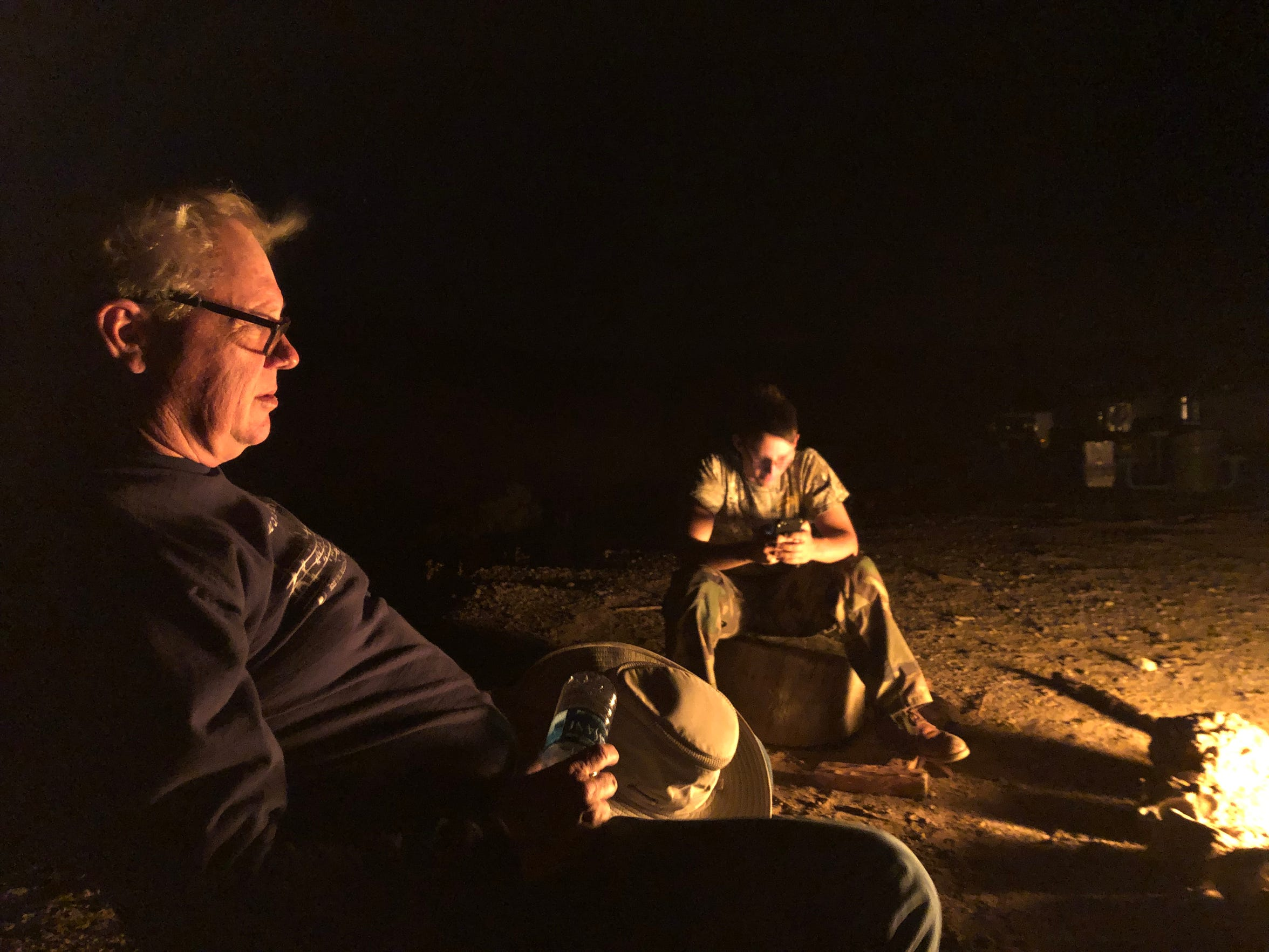 Cecil Pratt and his son, Caleb, sit by a campfire on the mountain. They slept on the mountain to be ready for sunrise.