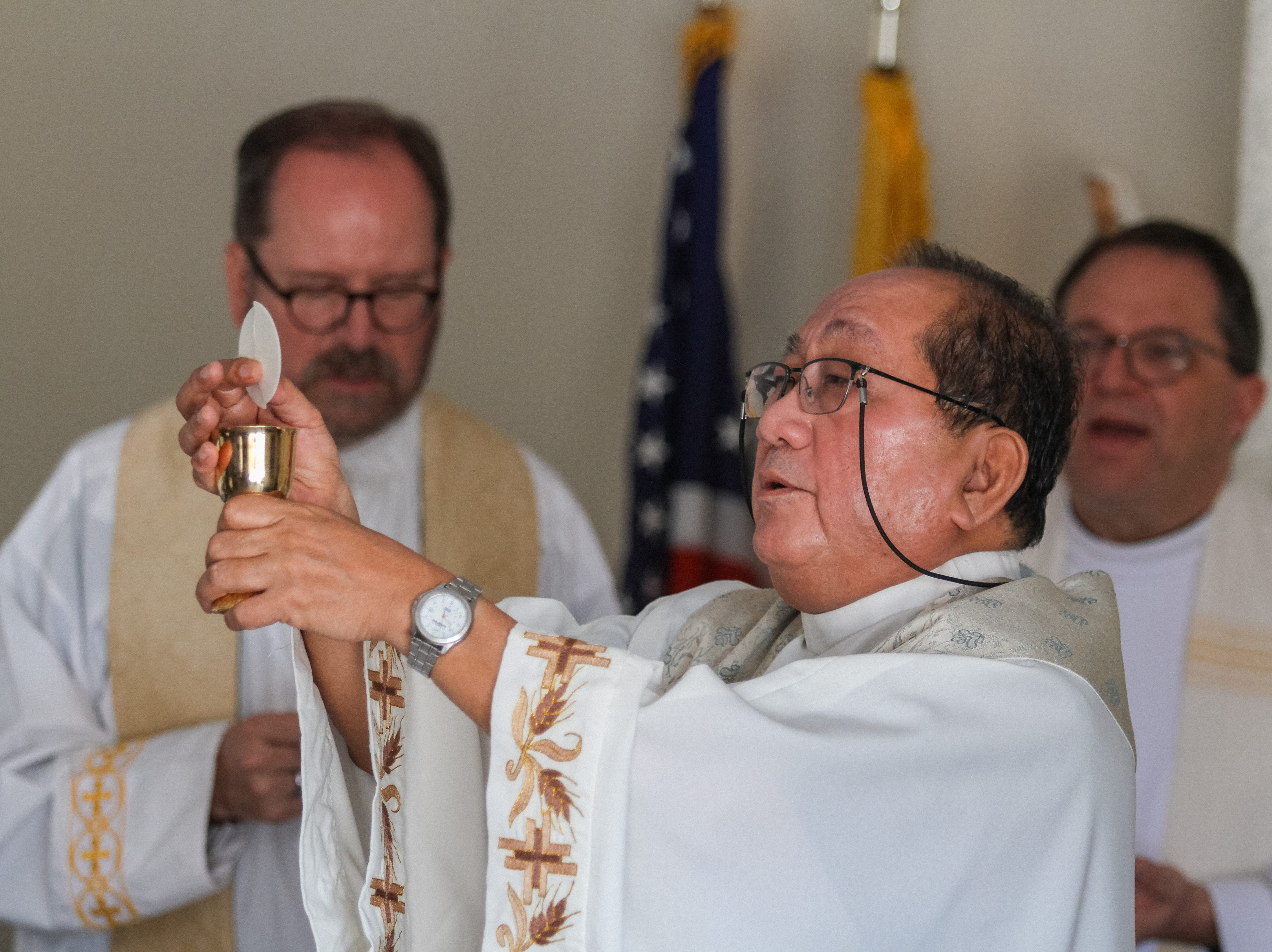 Rev. Reggie Carreon of St.  Joseph blesses the bread and wine for Mass hours after St. Joseph Catholic Church in Phoenix caught fire on May 1, 2019.