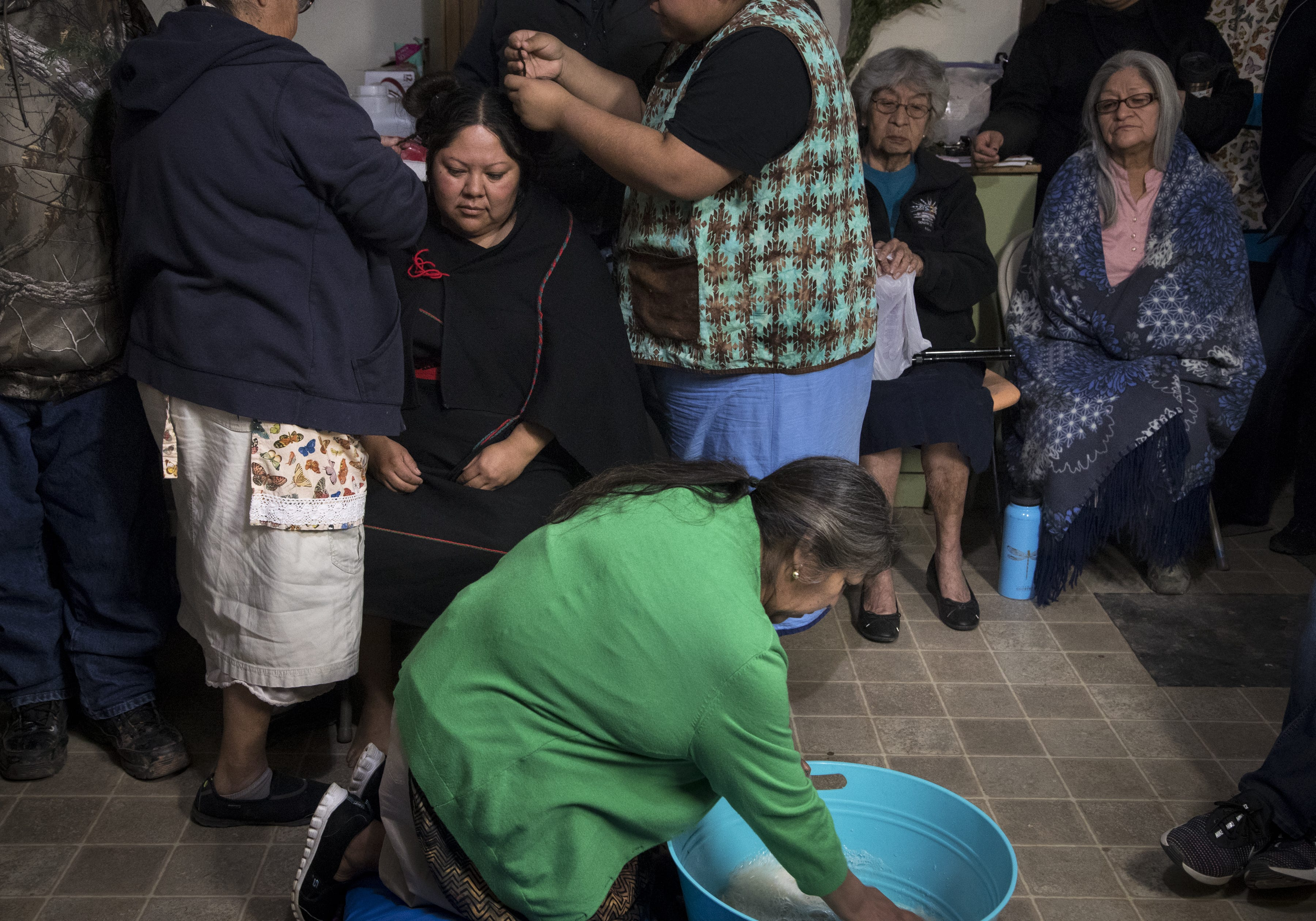 On the fifth day of the wedding, March 23, 2019, Sarah Honanie (in the green sweater) mixes yucca root with water, while Gloria Phillips (top left) takes Kara's hair down.