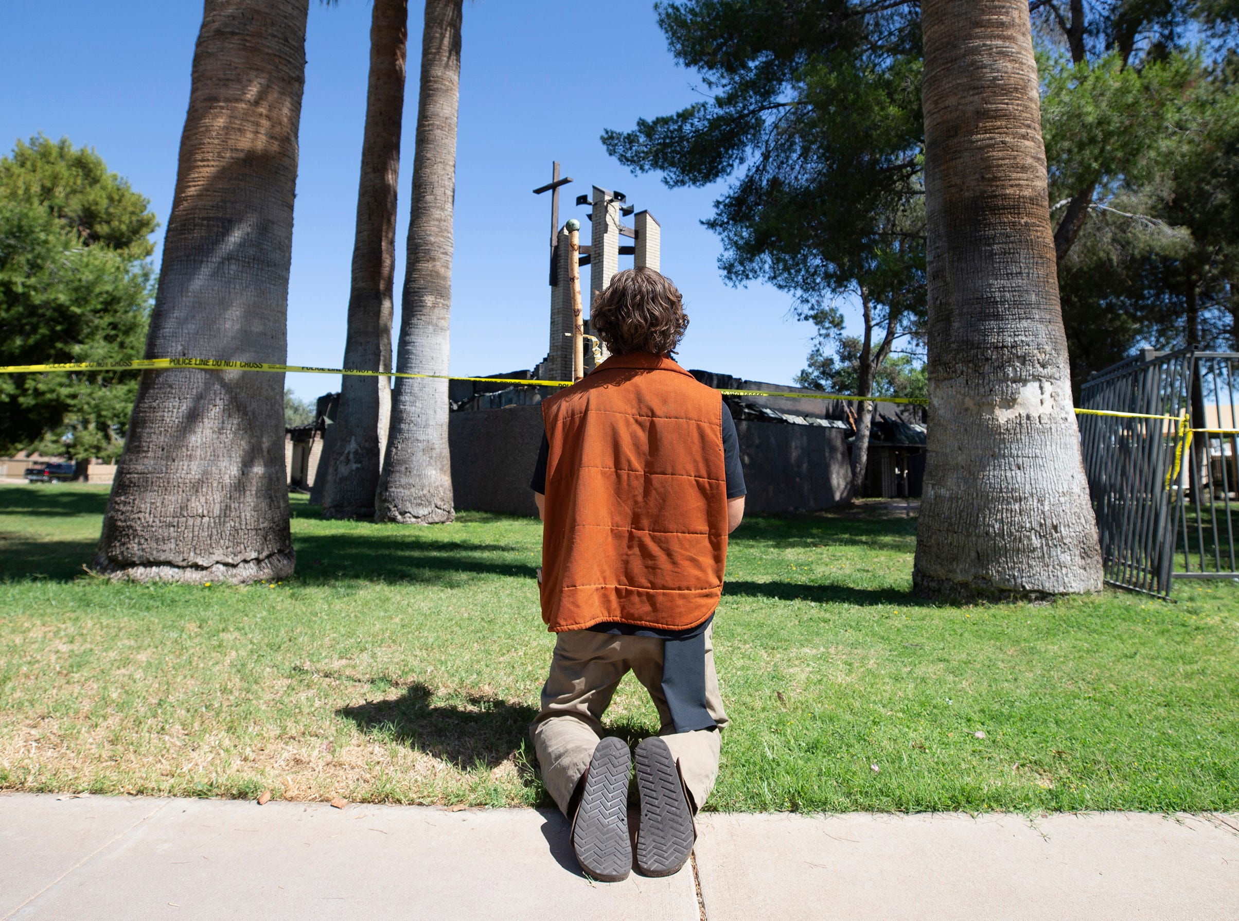 Joseph Pomarico of Phoenix prays outside St. Joseph Catholic Church in Phoenix on May 1, 2019, after a fire destroyed most of the church.