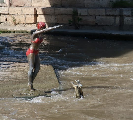 One of Skopje's many statues, in which a bikini-clad swimmer prepares to dive into the Vardar River. Another swimmer, feet protruding above the water, has already made a splash.