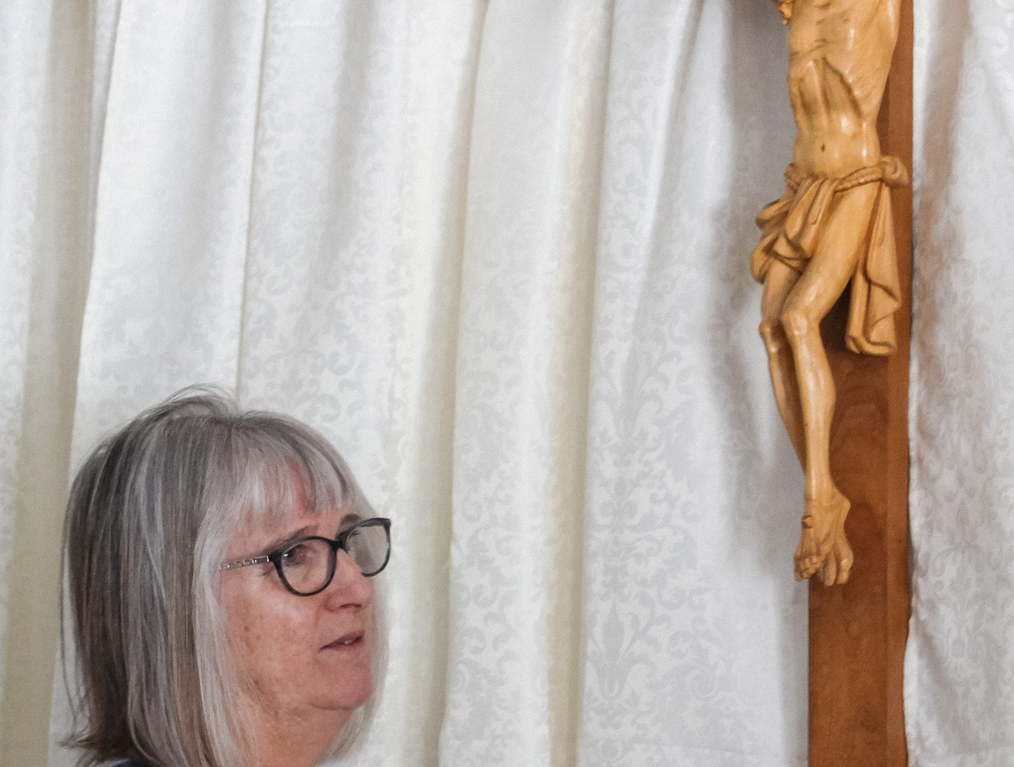 Teresa Caldera touches her late uncle's cross that she thought had she had lost in a fire that destroyed St. Joseph Catholic Church in Phoenix on May 1, 2019.