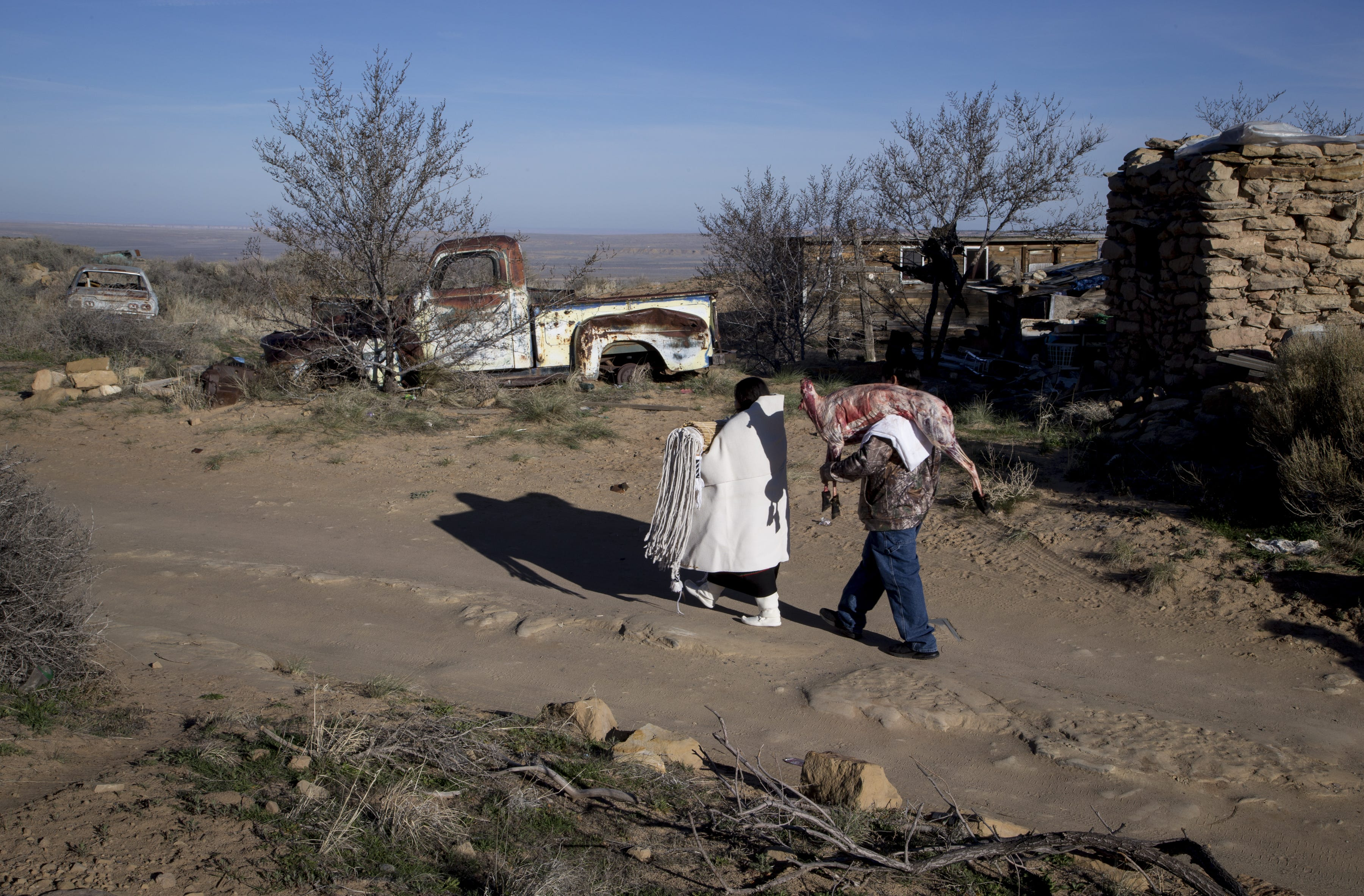 Wearing a black manta and a white cape, Kara walked up the road holding the bridal suitcase. Behind her, Lester carried a butchered sheep on March 28, 2019, in Hotevilla, Arizona.