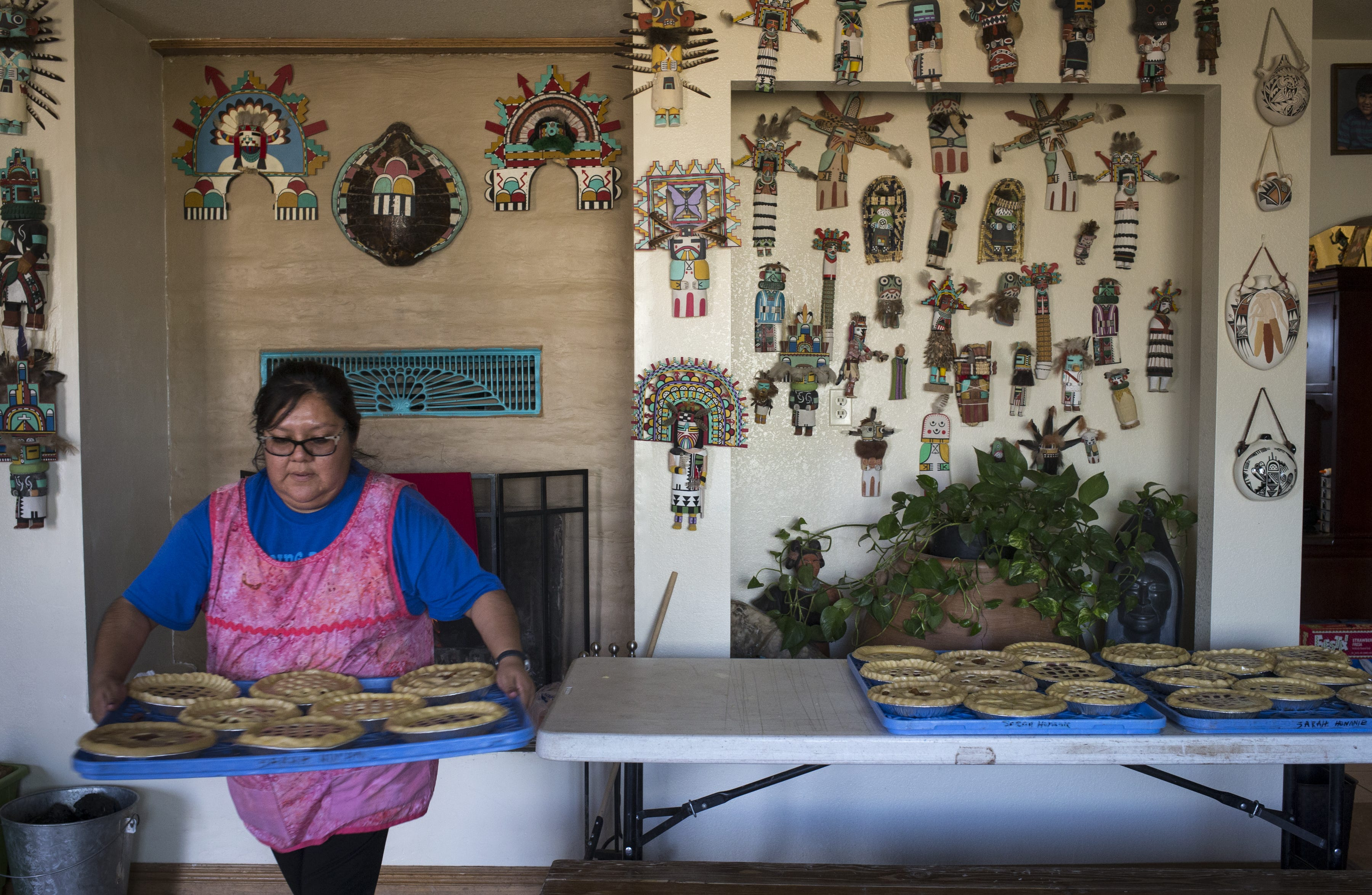 Tiah Honanie, the bride's sister, carries a tray of pies to be baked in the outdoor oven on March 21, 2019, in Hotevilla, Arizona.