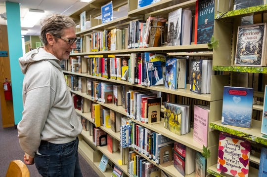 Dennie Hill looks over books at St. Clair County Library's main branch Wednesday, May 1, 2019 in Port Huron.