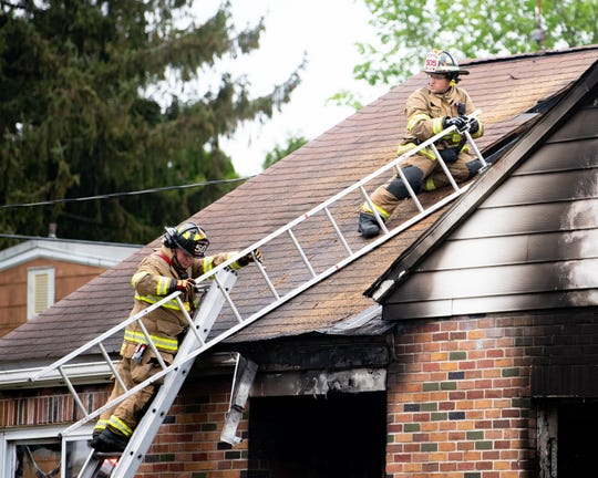 Firefighters inspect the roof after a house fire, which killed a woman, in West Manchester Township on Wednesday.