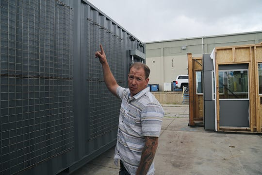 Chad Giguiere, owner of Twisted Metal in Reno, shows off siding that can be used to support vine plants for his shipping container-based housing concept on April 30, 2019.