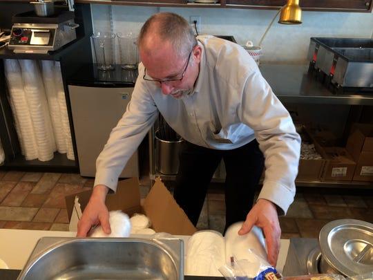 Bob Anderson stocks shelves for Corner Cafe at the Leland.