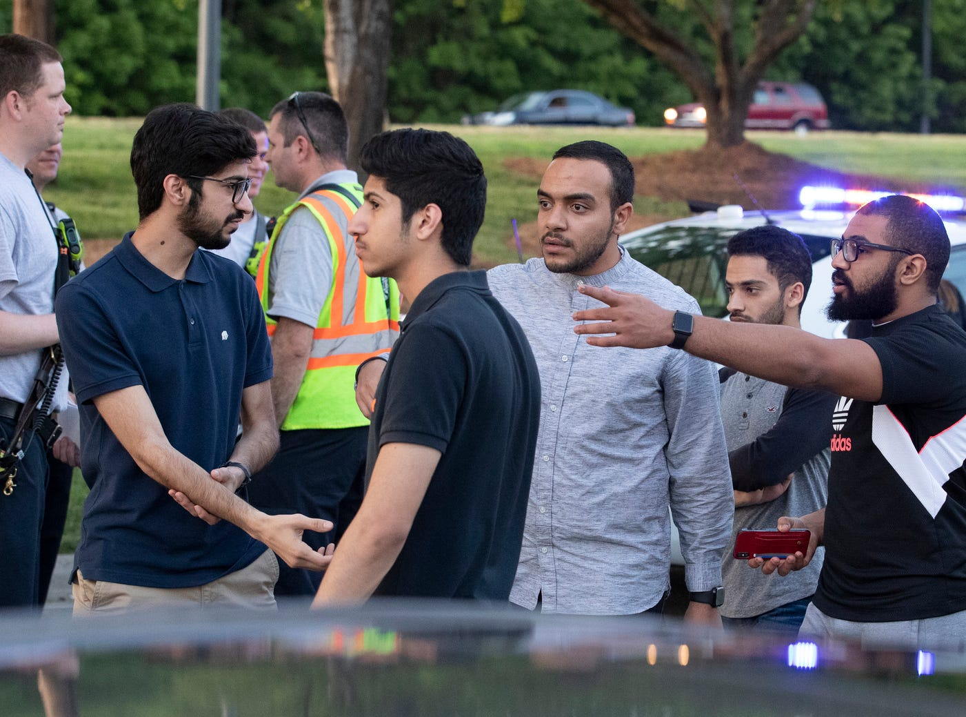 People gather across from the campus of University of North Carolina at Charlotte after a shooting at the school Tuesday, April 30, 2019, in Charlotte, N.C. The school shooting left at least a few people dead and several wounded Tuesday, prompting a lockdown and chaotic scene in the state's largest city.