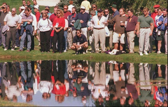 Golf fans gather around a pond near the 15th hole at Oak Hill Country Club.