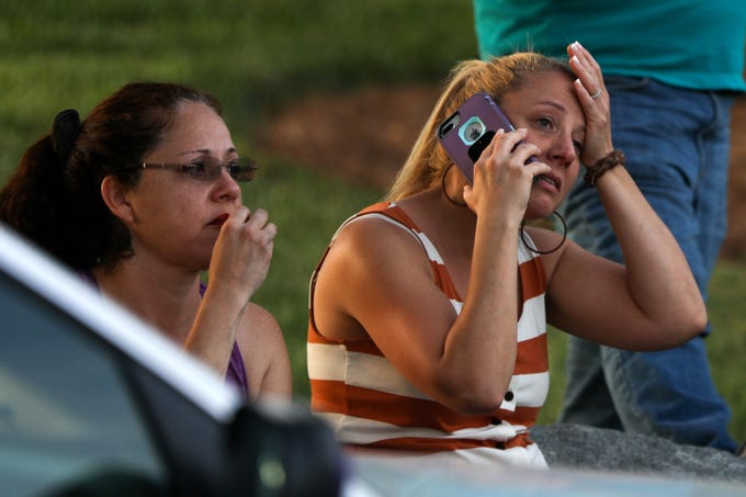 Family members and friends wait for their loved ones at a staging area after a shooting on the campus of University of North Carolina Charlotte in University City, Charlotte, on April 30, 2019. - At least two people were killed and several wounded in a shooting at the University of North Carolina's Charlotte campus, staff and local media reported.