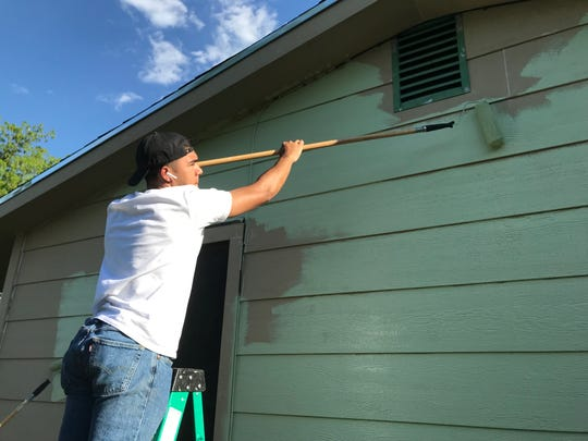 Gabriel Villanueva reaches for a patch at 1522 Wynne Ave. at the Neighborhood Painting Blitz on Saturday, April 27, 2019.